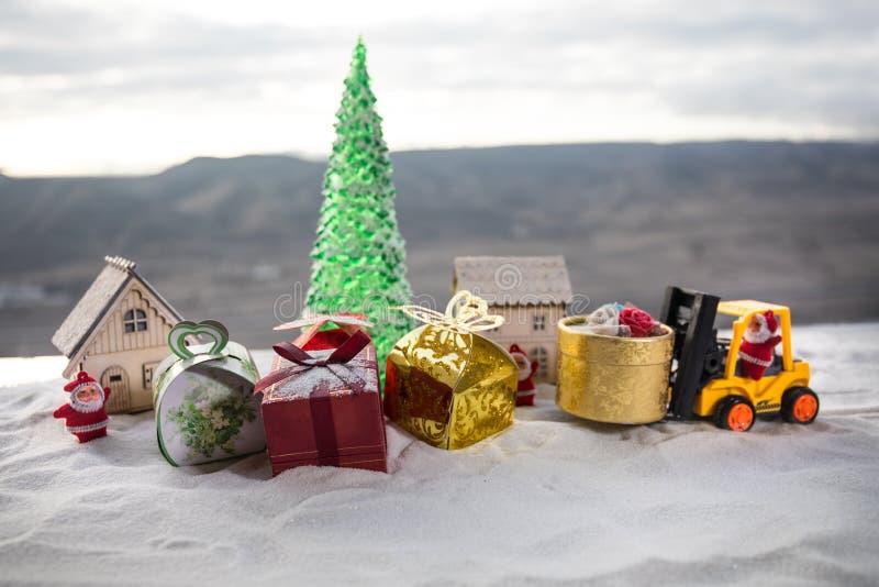 Caja de regalo miniatura por la máquina de la carretilla elevadora en nieve, imagen resuelta para el día de fiesta de la Navidad  imagen de archivo libre de regalías