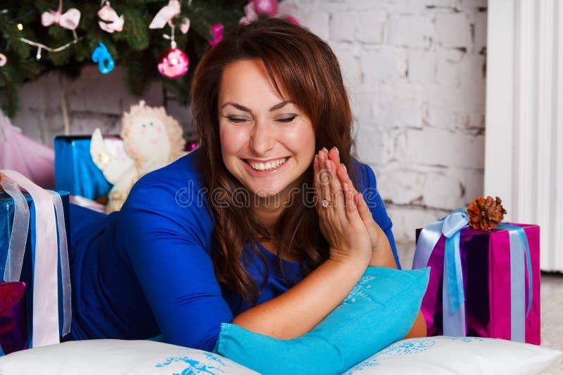 Caja de regalo morena joven feliz de la abertura de la mujer cerca del árbol de navidad fotos de archivo libres de regalías