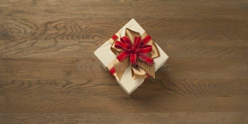 Caja de regalo de Navidad atada con un arco rojo y dorado sobre una mesa de madera imagen de archivo