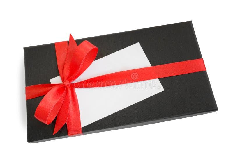 Caja de regalo negra con el arco rojo de la cinta de satén y una tarjeta en blanco imagenes de archivo