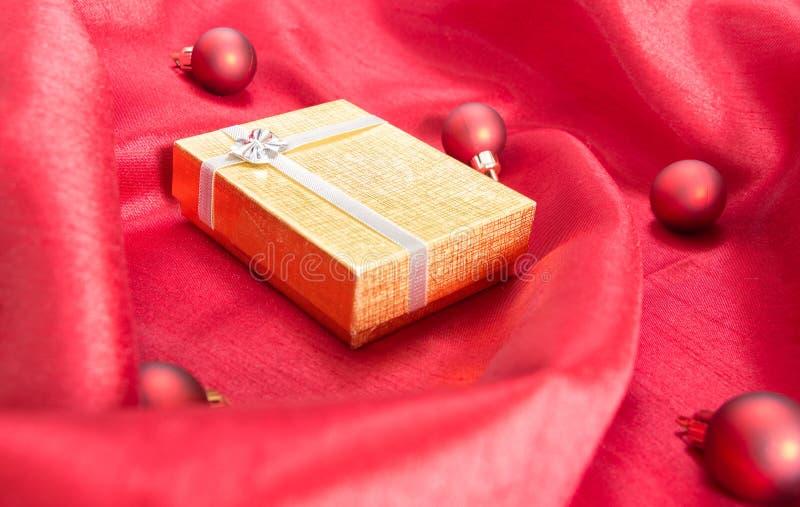 Caja de regalo de oro con el arco, en la tela de satén ondulada roja con las bolas de la Navidad imágenes de archivo libres de regalías