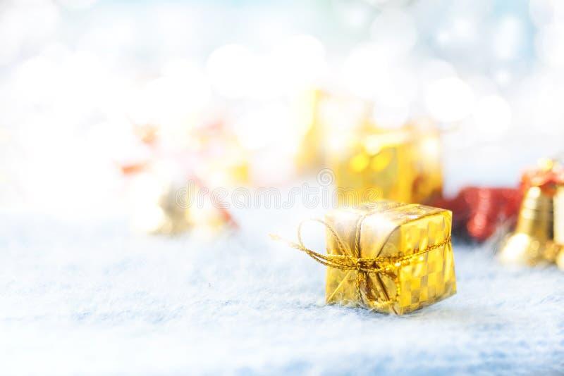 Caja de regalo de oro debajo del árbol de navidad en un fondo azul snowing foto de archivo
