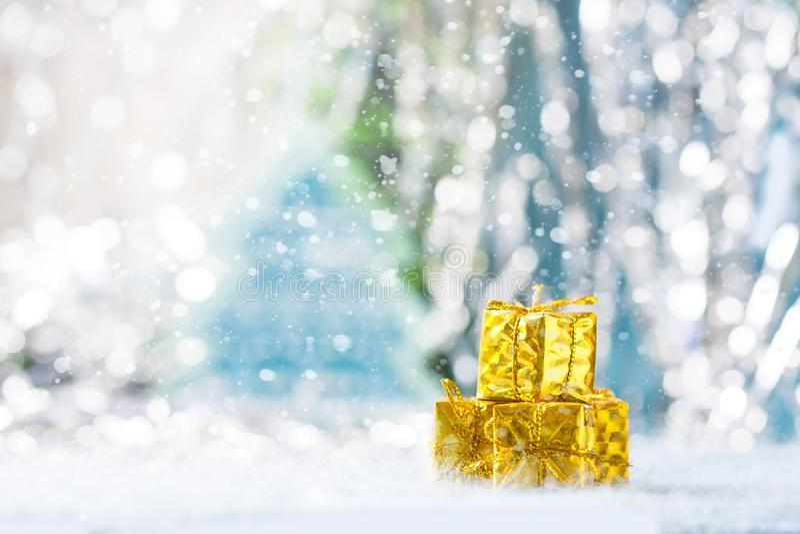 Caja de regalo de oro debajo del árbol de navidad en un fondo azul snowing fotografía de archivo libre de regalías