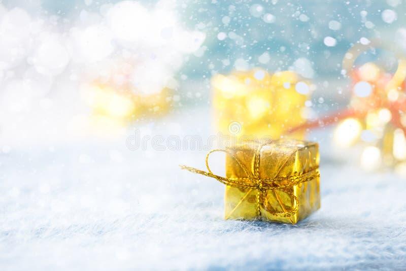 Caja de regalo de oro debajo del árbol de navidad en un fondo azul snowing fotos de archivo