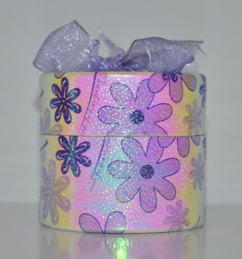 Caja de regalo púrpura que brilla intensamente con un arco fotos de archivo
