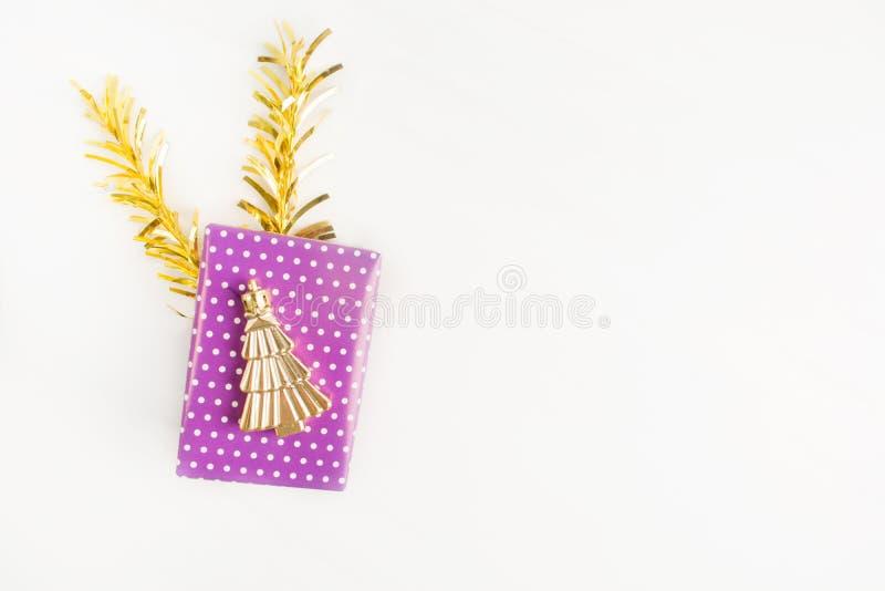 Caja de regalo púrpura violeta con el árbol del símbolo de la Navidad en él con la decoración de oro en fondo ligero foto de archivo