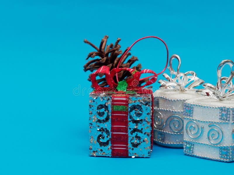 Caja de regalo de plata brillante blanca con la cinta roja y arco con el cono de plata de la caja y del pino de la casilla blanca fotografía de archivo libre de regalías