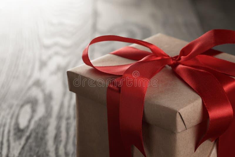 Caja de regalo rústica con el arco rojo de la cinta fotos de archivo libres de regalías