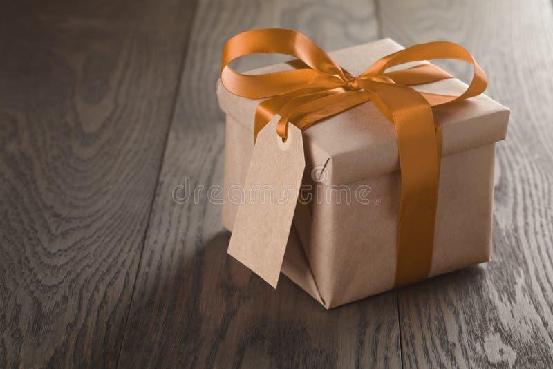 Caja de regalo rústica con el arco y el Empty tag anaranjados de la cinta fotos de archivo