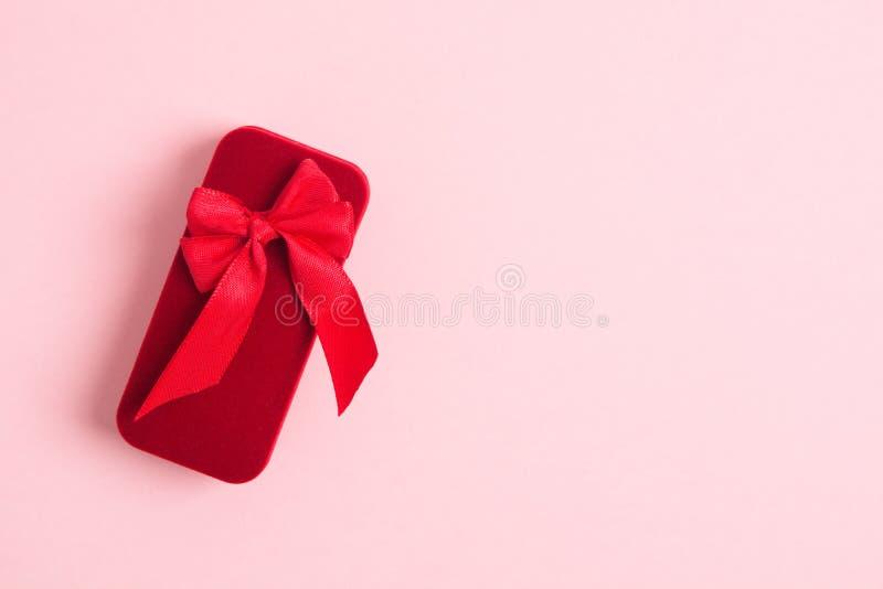 Caja de regalo roja del día de fiesta para la joyería con el arco rojo en fondo rosado con el espacio de la copia imágenes de archivo libres de regalías
