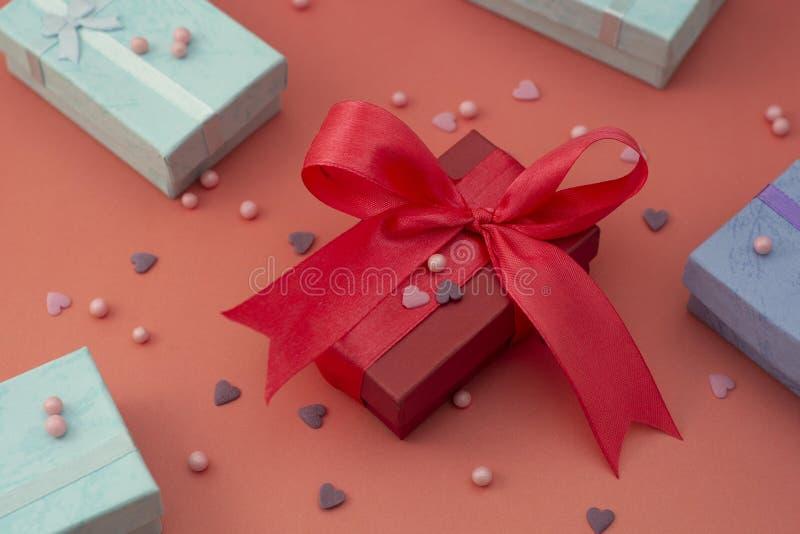Caja de regalo roja, rosada con el arco grande, en tablero rojo o rosado colorido Visión superior con el espacio de la copia Cump imágenes de archivo libres de regalías