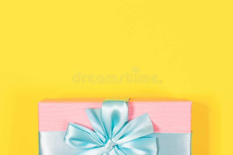 Caja de regalo rosada atada con la cinta azul con el arco en el top en fondo amarillo Copie el espacio para el texto Endecha míni fotografía de archivo libre de regalías