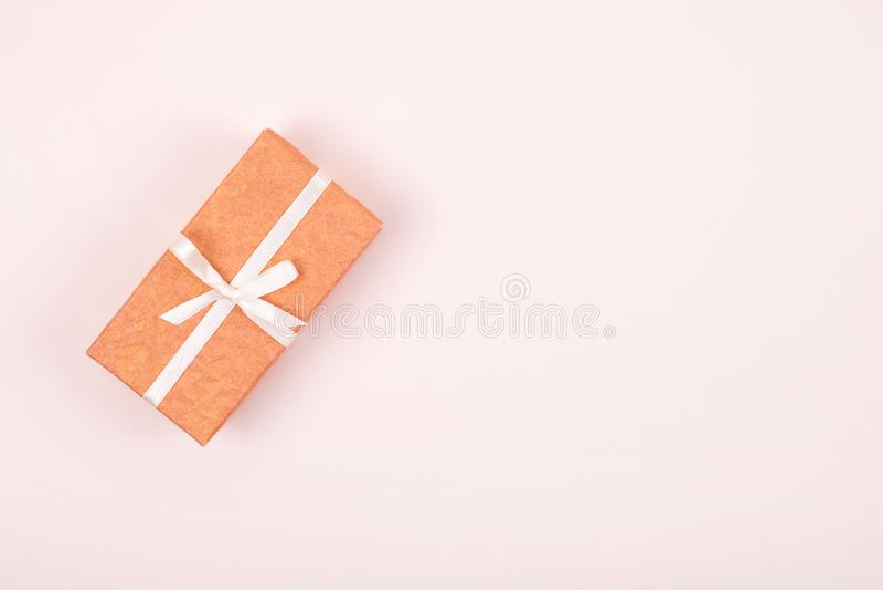 Caja de regalo simple adornada con la cinta blanca del arco en fondo rosado en colores pastel Endecha plana fotografía de archivo libre de regalías
