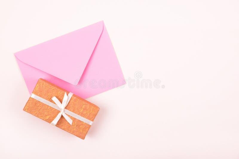 Caja de regalo simple adornada con la cinta blanca del arco y el sobre rosado en fondo en colores pastel Endecha plana fotos de archivo