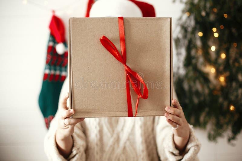 Caja de regalo simple de la Navidad con la cinta roja en manos de la muchacha feliz elegante en el sombrero de santa en fondo del foto de archivo