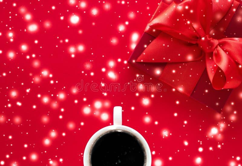 Caja de regalo de vacaciones de invierno, taza de café y nieve que brilla intensamente en el fondo flatlay rojo, sorpresa del tie foto de archivo