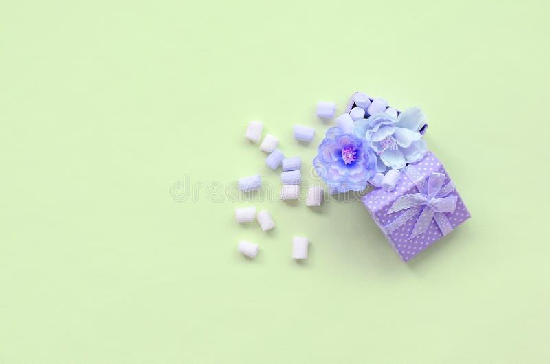 Caja de regalo violeta florecida asperjada con las melcochas en fondo de la cal imagen de archivo