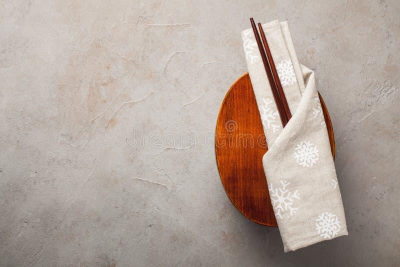 Caja del almuerzo japonesa de madera cerrada con los palillos, envueltos en un paño festivo en una tabla de piedra vieja Visión s imagenes de archivo