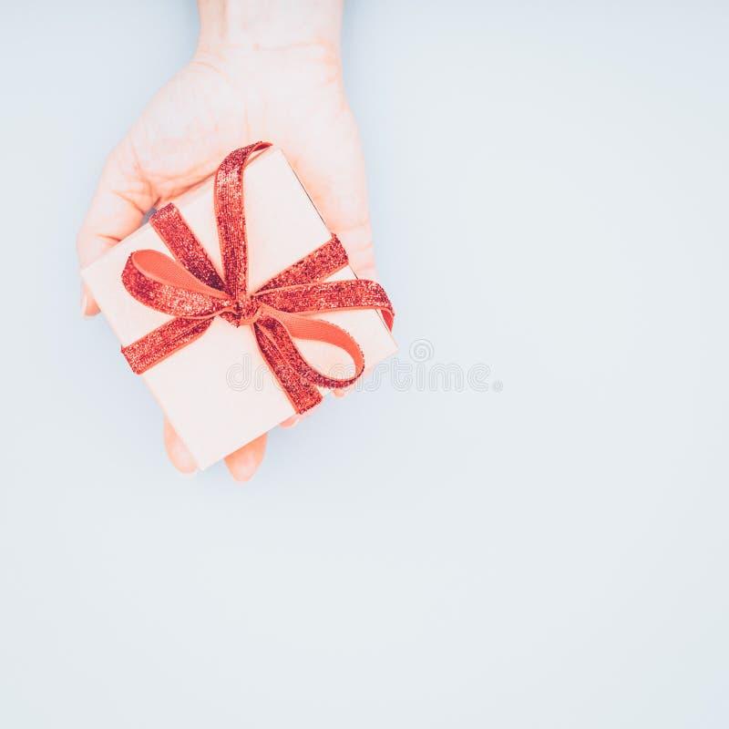Caja del arte con el arco rojo de la cinta en mano femenina Día de San Valentín concentrado imagen de archivo