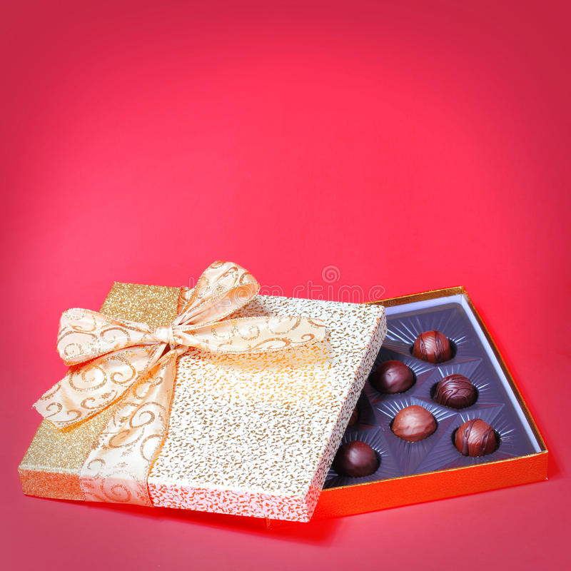 Caja del caramelo del oro con las trufas sobre fondo rojo. Navidad imágenes de archivo libres de regalías