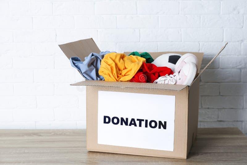 Caja del cartón con donaciones en la tabla imagen de archivo