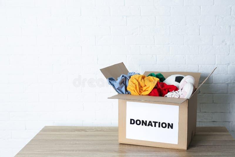 Caja del cartón con donaciones en la tabla cerca de la pared de ladrillo fotos de archivo libres de regalías