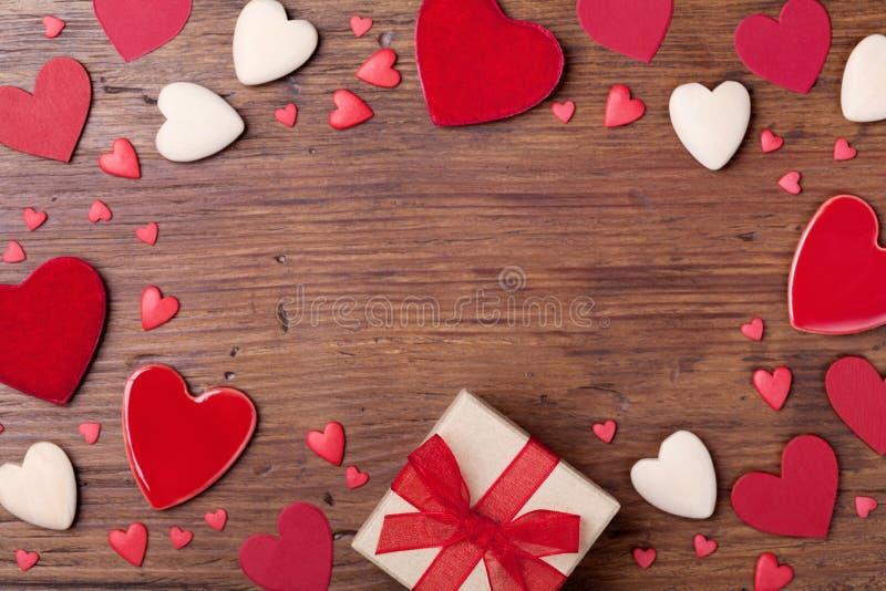 Caja del presente o de regalo y corazones mezclados para el marco del día de tarjetas del día de San Valentín Visión superior Fon imagenes de archivo