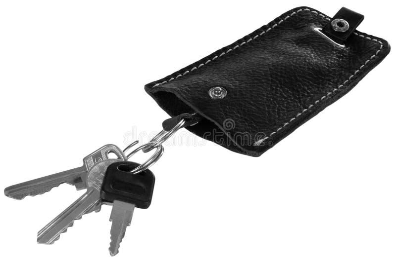 Caja dominante de cuero negra con llaves aislada en el fondo blanco imágenes de archivo libres de regalías