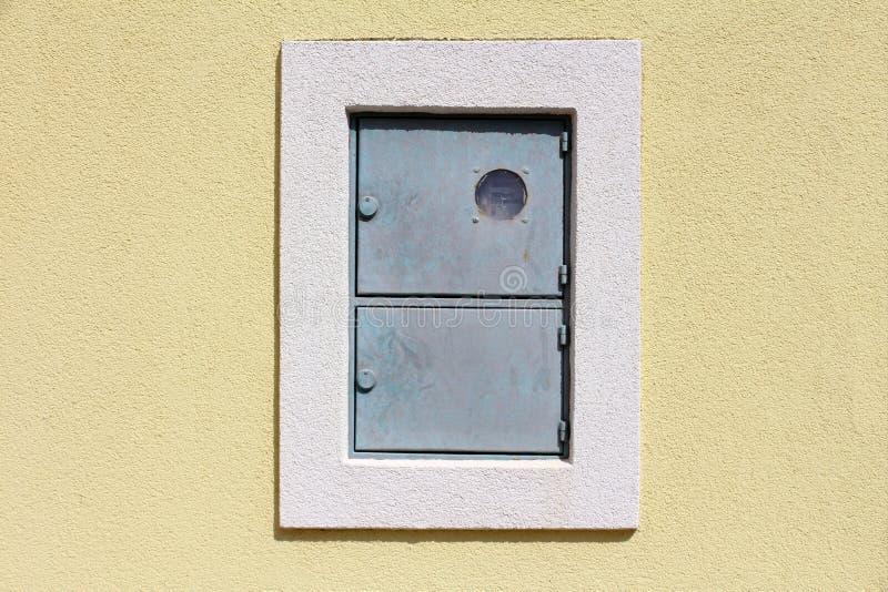 Caja eléctrica del metro del metal bloqueado al aire libre con la caja de interruptor montada en la pared de la casa con la nueva imagen de archivo libre de regalías