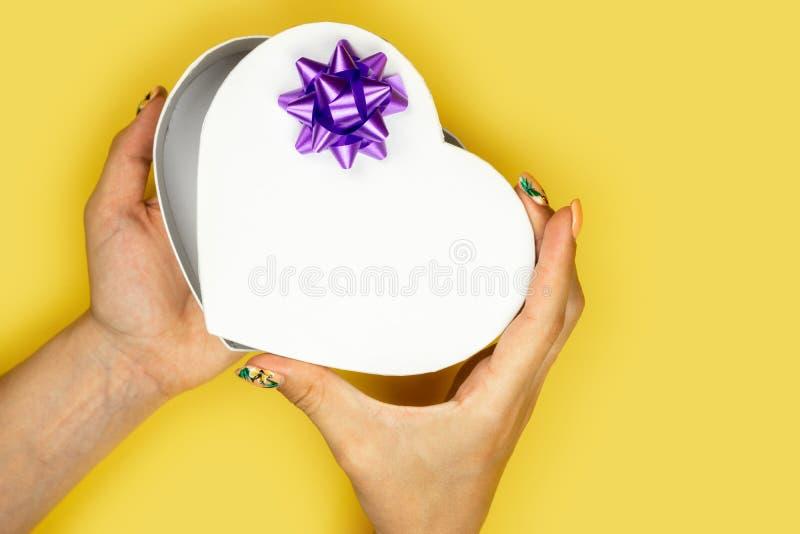 Caja en forma de corazón abierta de la mujer en fondo amarillo Concepto del amor del d?a de tarjetas del d?a de San Valent?n foto de archivo