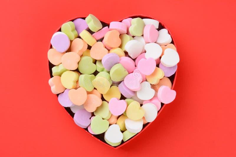 Caja en forma de corazón con el caramelo de las tarjetas del día de San Valentín fotos de archivo