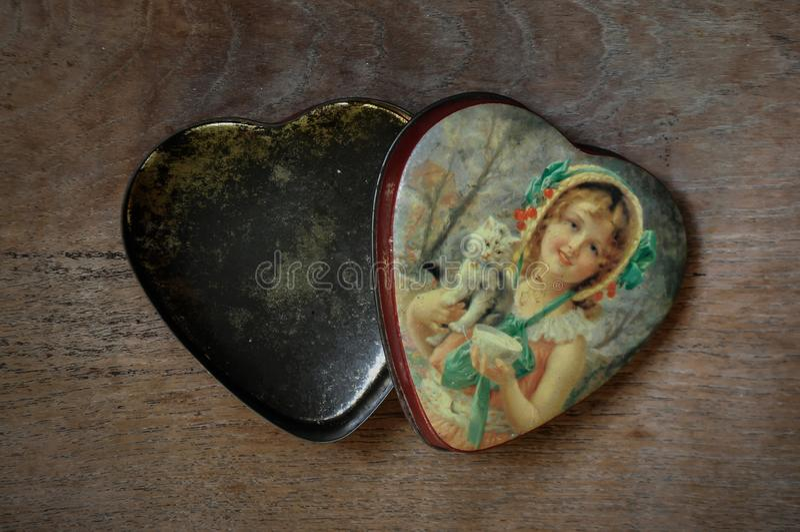Caja en forma de corazón de la lata del vintage en viejo fondo de madera foto de archivo