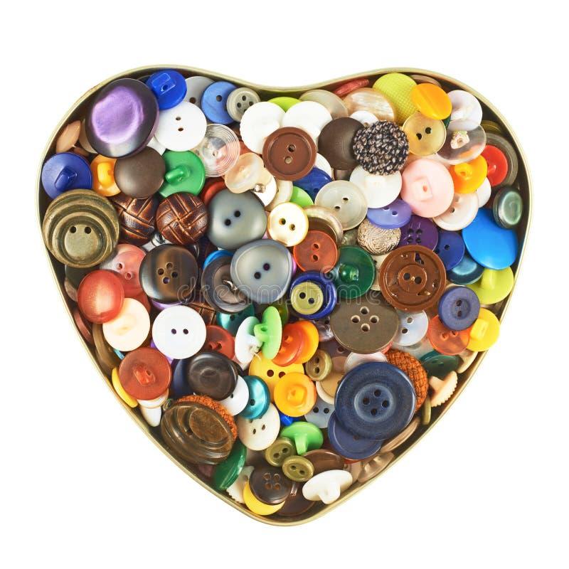 Caja en forma de corazón llenada de los botones foto de archivo libre de regalías