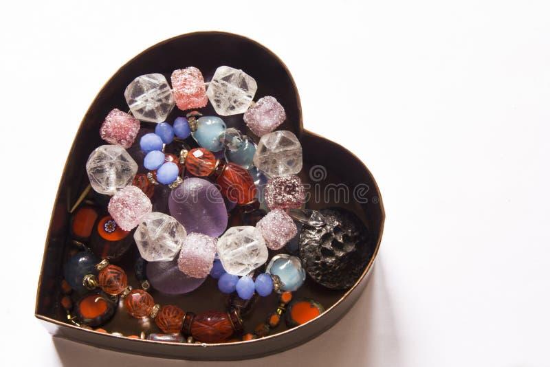 Caja en forma de corazón llenada de la joya y de las gotas fotografía de archivo libre de regalías