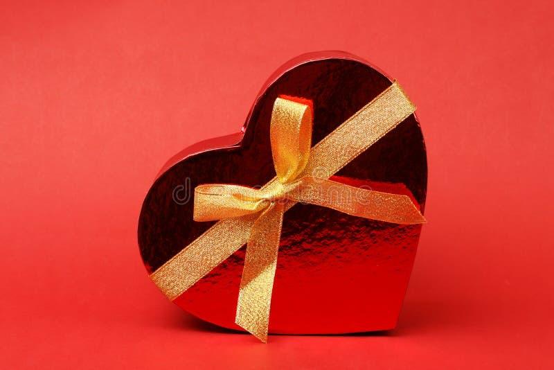 Caja en forma del corazón con el arco en fondo rojo fotografía de archivo libre de regalías