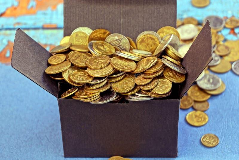 caja negra por completo de monedas amarillas que se colocan en una tabla azul fotografía de archivo libre de regalías
