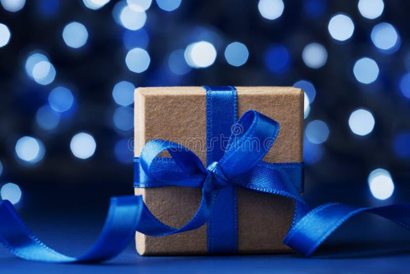 Caja o presente de regalo de la Navidad con la cinta del arco contra fondo azul del bokeh Tarjeta de felicitación mágica del día  imágenes de archivo libres de regalías