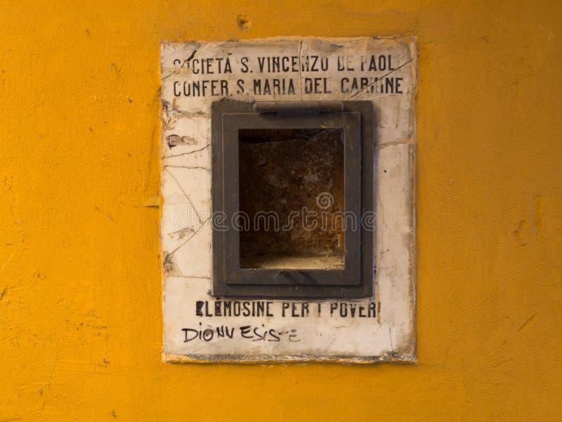 Caja pobre en una pared ocre fotografía de archivo