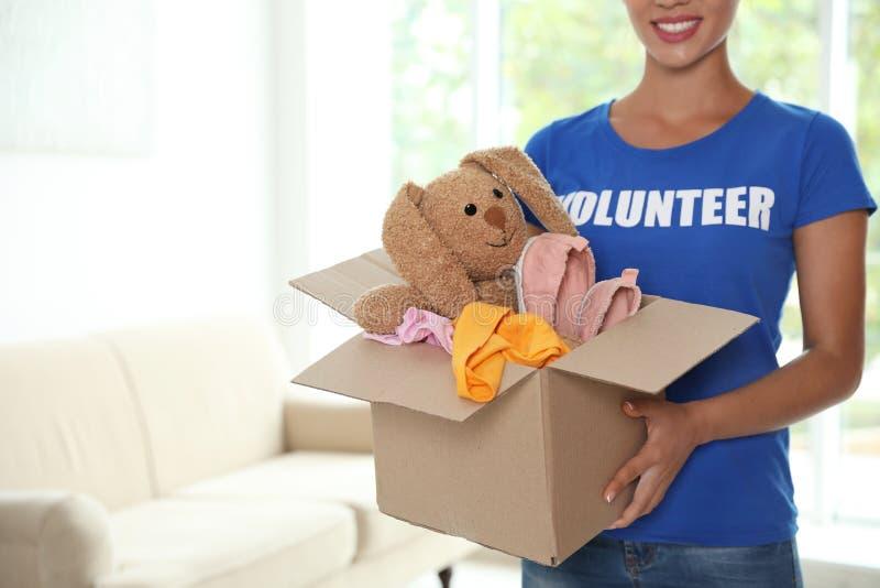 Caja que se sostiene voluntaria de la hembra con donaciones dentro imagen de archivo libre de regalías
