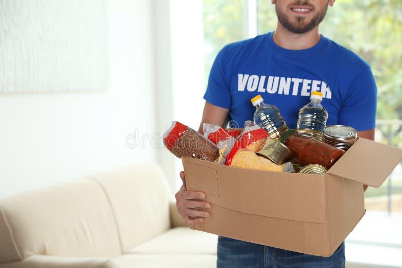 Caja que se sostiene voluntaria del varón con donaciones dentro fotografía de archivo