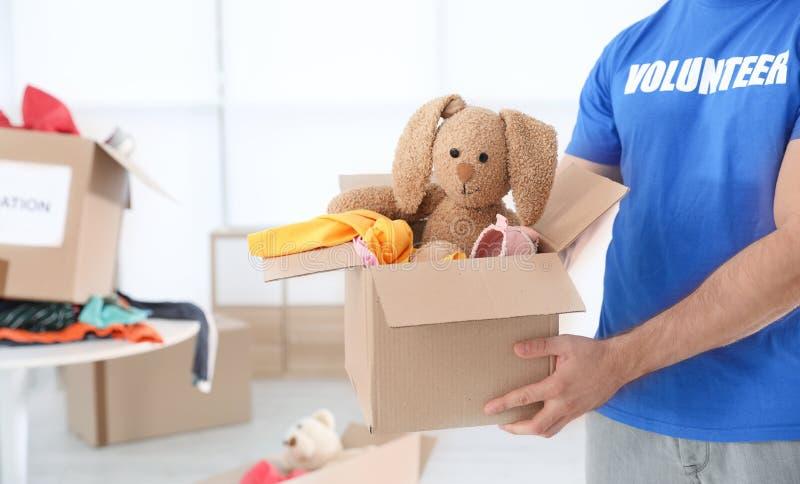 Caja que se sostiene voluntaria del varón con donaciones dentro imagen de archivo libre de regalías