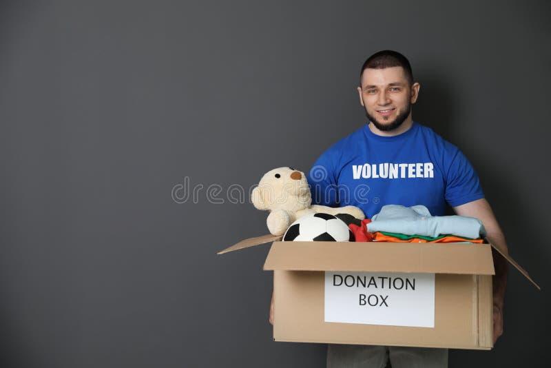 Caja que se sostiene voluntaria masculina con donaciones foto de archivo libre de regalías