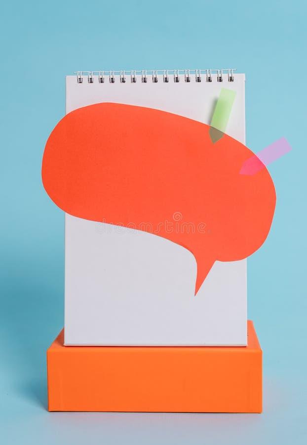 Caja rectangular permanente de la libreta del discurso de la burbuja de las banderas espirales en blanco de la flecha sobre fondo imagen de archivo libre de regalías