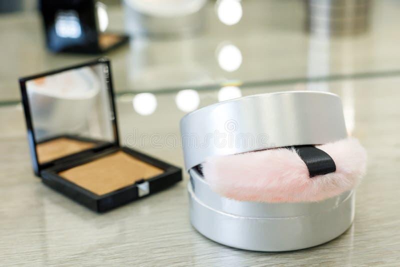 Caja redonda con el polvo y la esponja rosada de la piel y colorete en una caja cuadrada en un salón de belleza foto de archivo libre de regalías