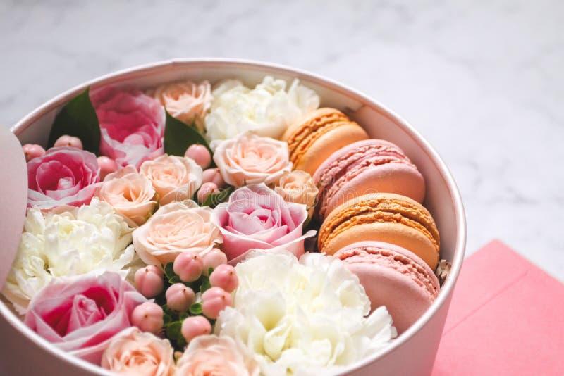Caja redonda del regalo con las flores, las rosas y la torta de la almendra de los macarrones con el sobre rosado en la tabla imagen de archivo libre de regalías