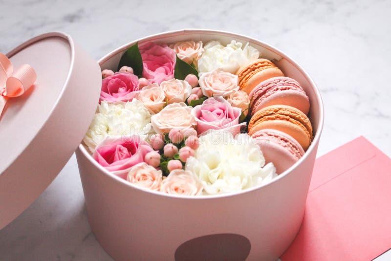 Caja redonda del regalo con las flores, las rosas y la torta de la almendra de los macarrones con el sobre rosado en la tabla fotos de archivo libres de regalías