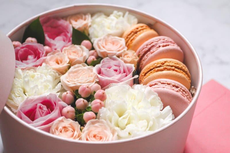 Caja redonda del regalo con las flores, las rosas y la torta de la almendra de los macarrones con el sobre rosado en la tabla imagen de archivo