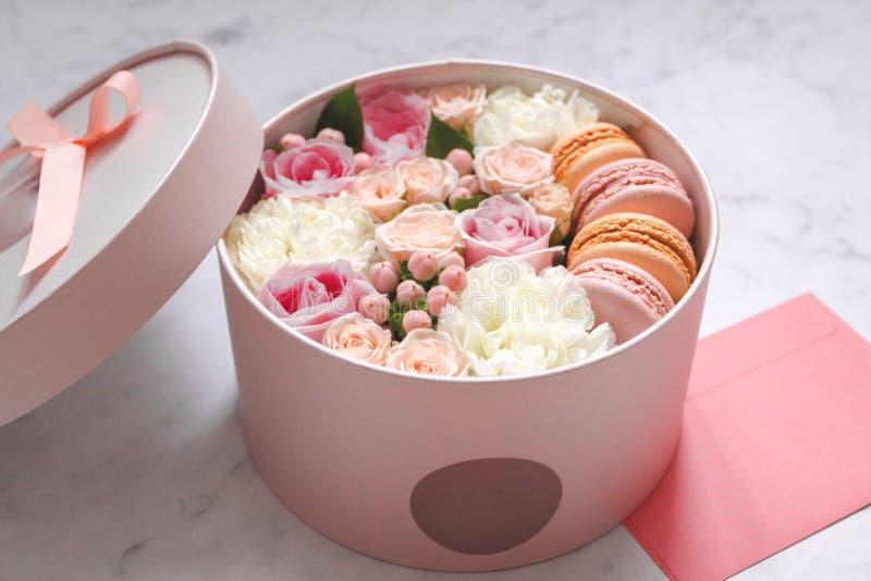 Caja redonda del regalo con las flores, las rosas y la torta de la almendra de los macarrones con el sobre rosado en la tabla imágenes de archivo libres de regalías