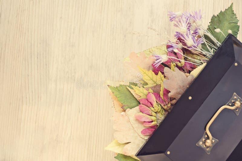 Caja retra con los detalles forjados, debajo de las hojas de otoño brillantes de la cubierta y de las flores salvajes Humor román fotografía de archivo