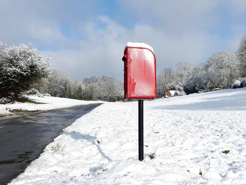 Caja roja del poste, carril de la perrera del perro, Chorleywood en nieve del invierno imagen de archivo